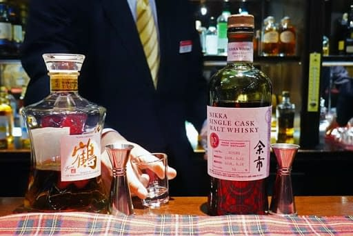 A bartender pouring a whisky for a businessman at a Japanese bar.