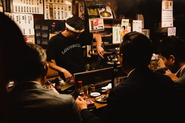 A Japanese bartender pouring drinks for colleagues at a nomikai gathering.