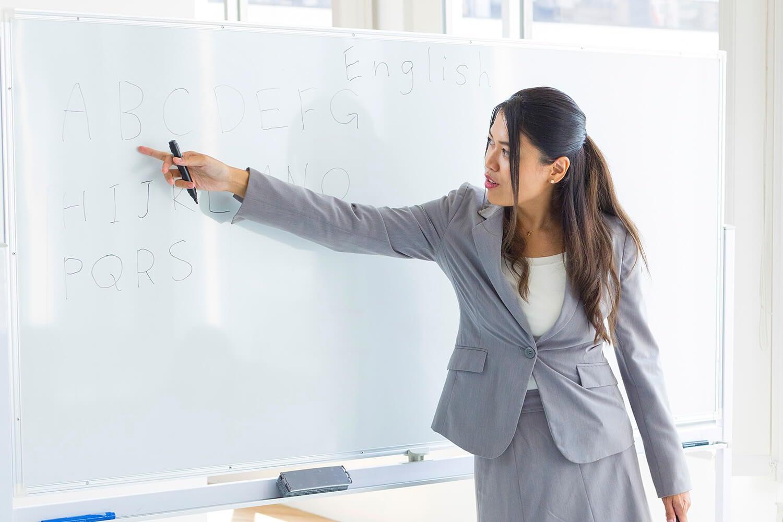 Women teacher teaching the alphabet on a whiteboard